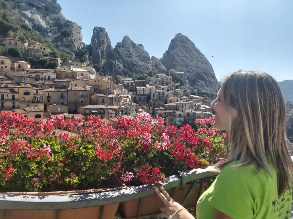 Sara la guida turistica ammira il panorama su Castelmezzano che è visibile dalla piazza del paese