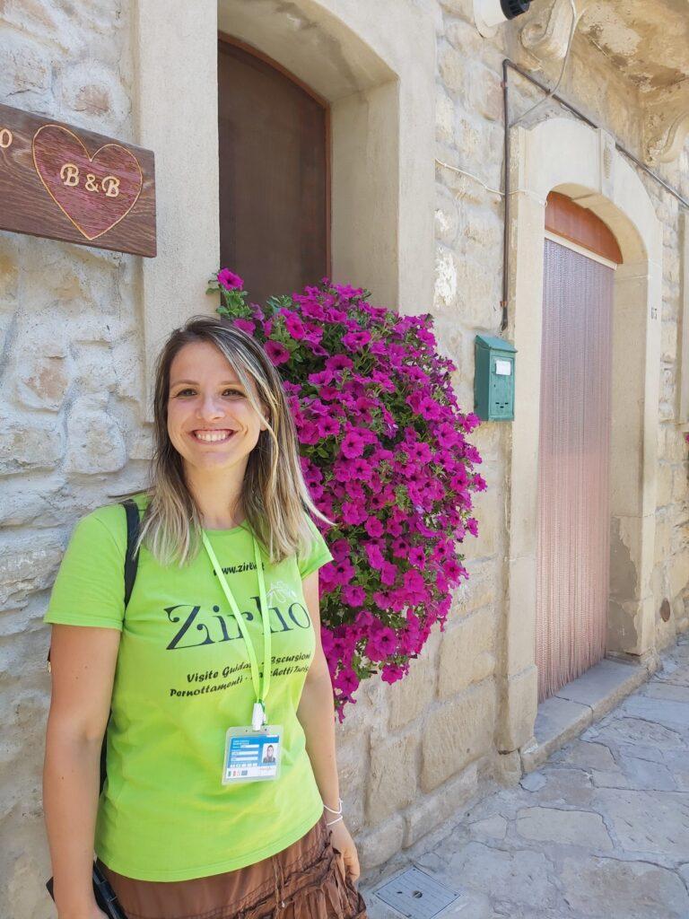 Sara la guida turistica sorride nel centro storico di Castelmezzano sotto l'insegna di un B&B romantico