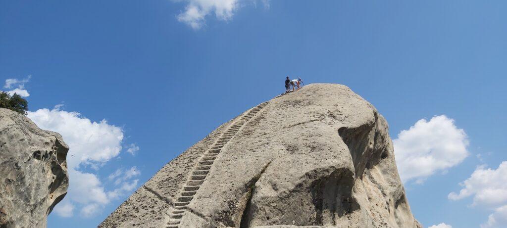 La sommità della fortezza normanna di Castelmezzano con dei turisti intenti a scalare la roccia imbracati di tutto punto